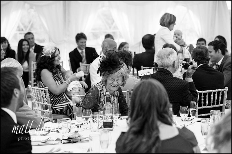 Lady laughing during wedding speeches in marquee