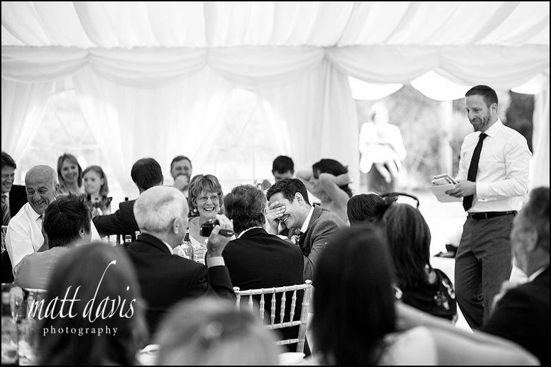 Groom with head in hand during speeches.  Photo in black and white