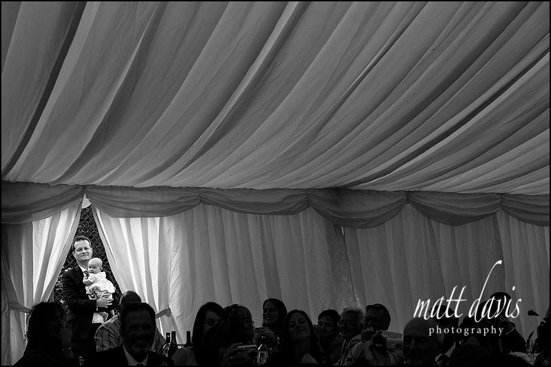 Man and baby at wedding in marquee stood by doorway.
