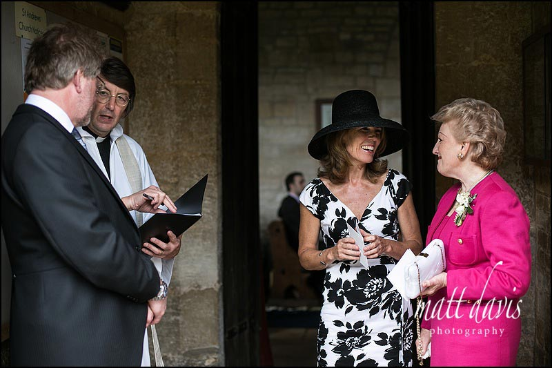 Wedding guests outside St Andrew's church Naunton, Gloucestershire