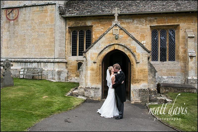 wedding couple kissing outside St Andrew's church near Cheltenham