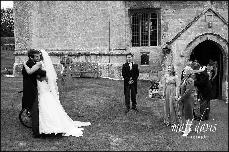 Documentary photo of wedding guests outside Naunton church