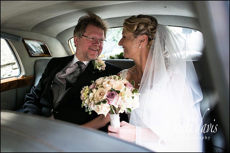 Wedding couple in wedding car smiling at each other