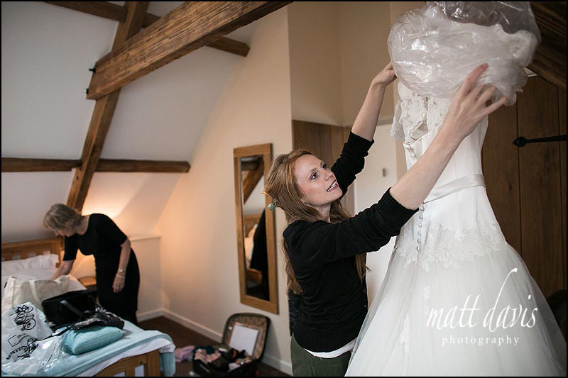 Bride taking wedding dress out of packaging
