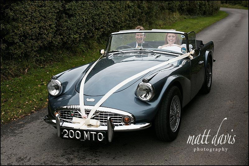 Classic wedding car arriving at Kingscote Barn