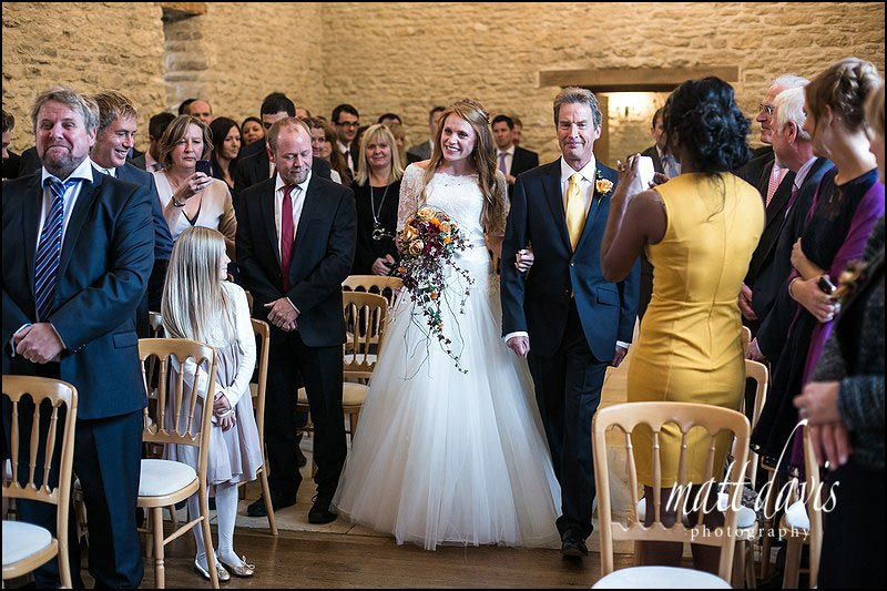 Bride walking down the aisle at Kingscote Barn