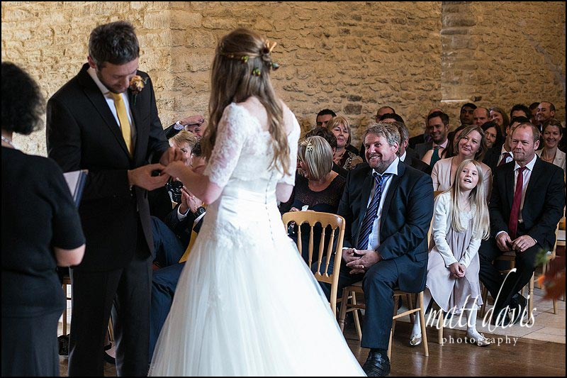 Bride & groom exchange of rings wedding photos at Kingscote Barn