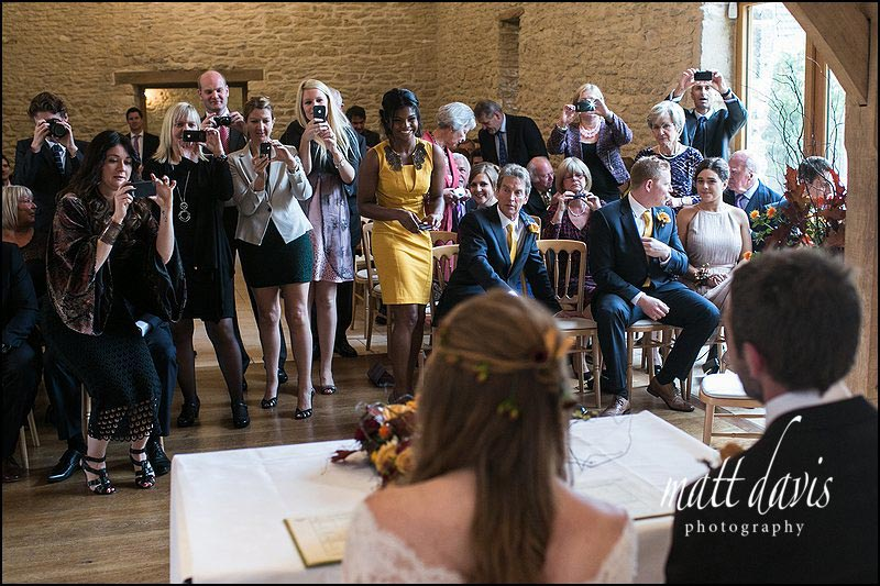 Bride & groom signing the wedding register at Kingscote Barn