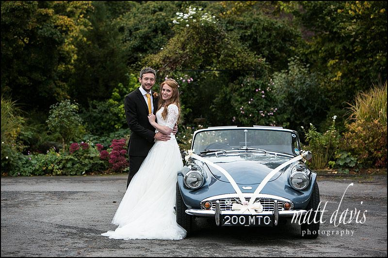 Classic wedding photography of bride and groom with wedding car at Kingscote Barn