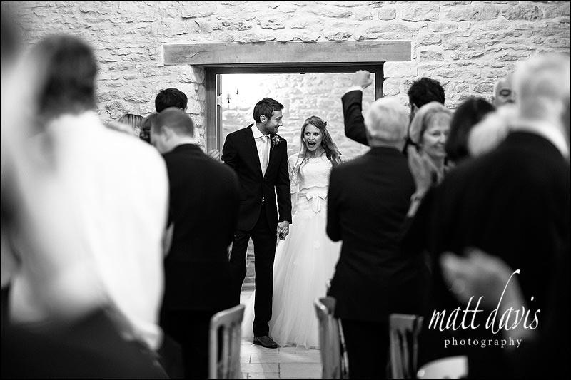 Kingscote Barn wedding photography as couple enter wedding breakfast