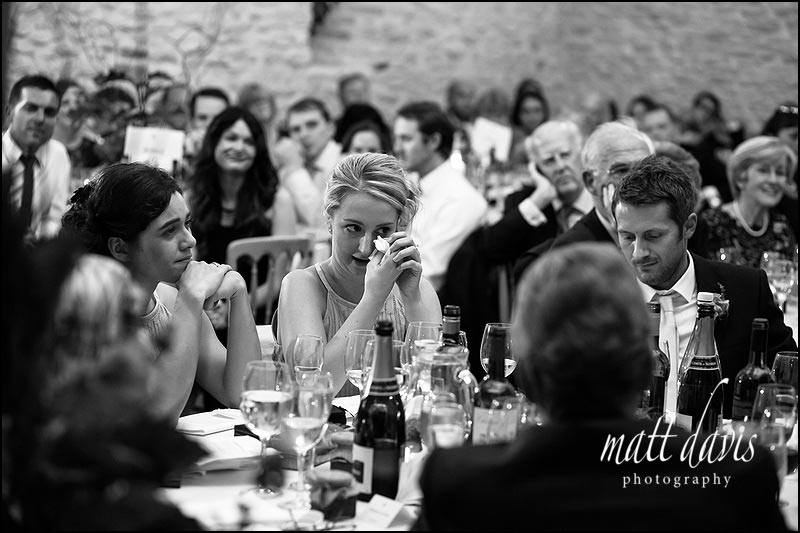bridesmaid with tear in her eye during speeches at Kingscote Barn wedding