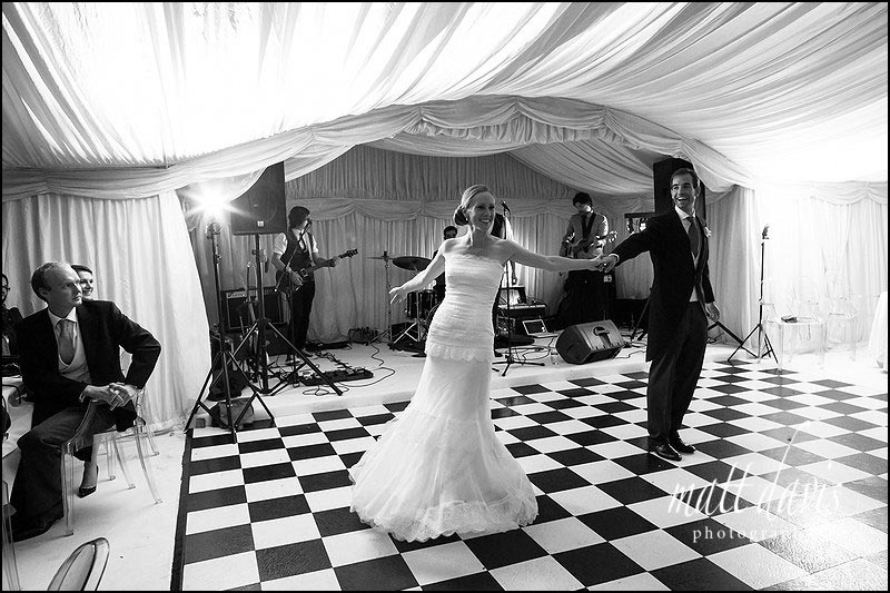 Wedding Photographer Gloucestershire captures first dance in marquee with checker dance flooring.