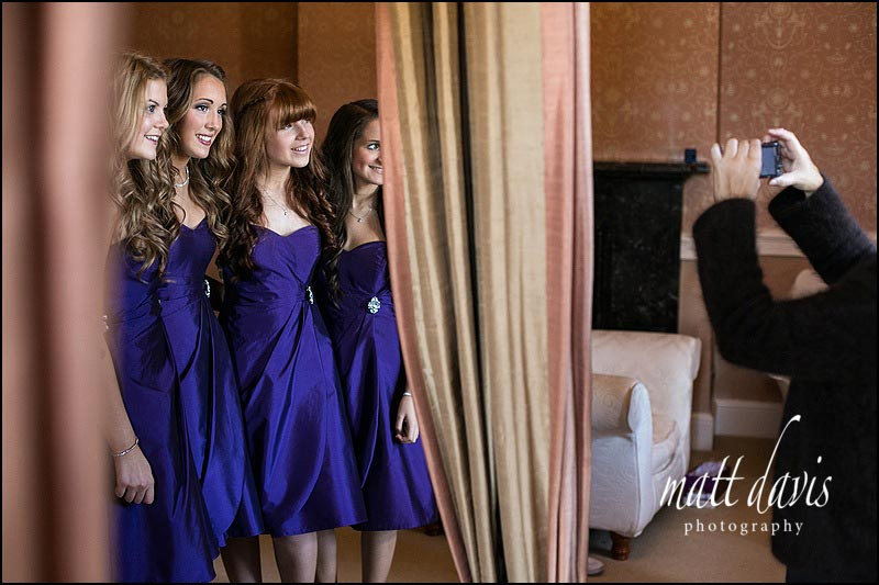 bridesmaids in purple bridesmaid dresses being photographed at Clearwell Castle