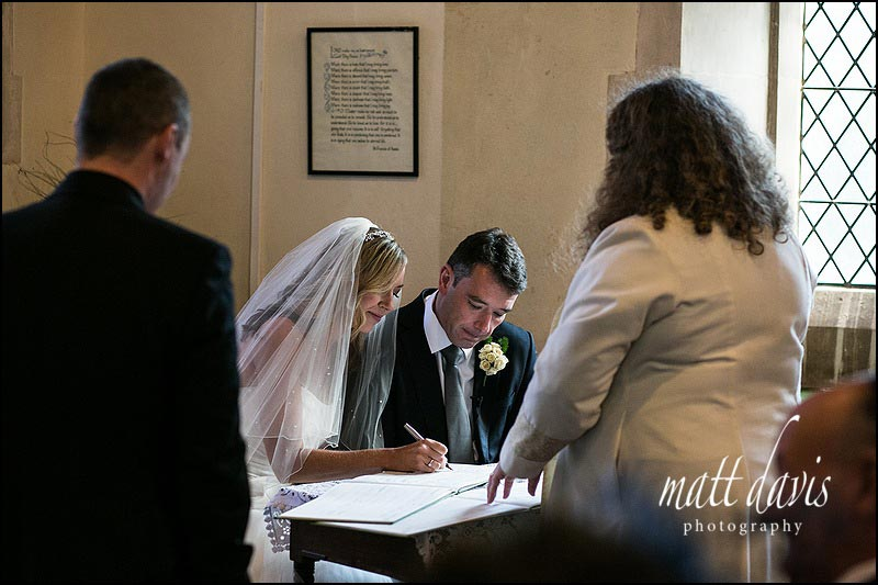 Photos inside St Peter's church, Clearwell, Gloucestershire of bride and groom signing the wedding register