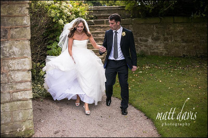 bride and groom holding hands in Clearwell Castle gardens