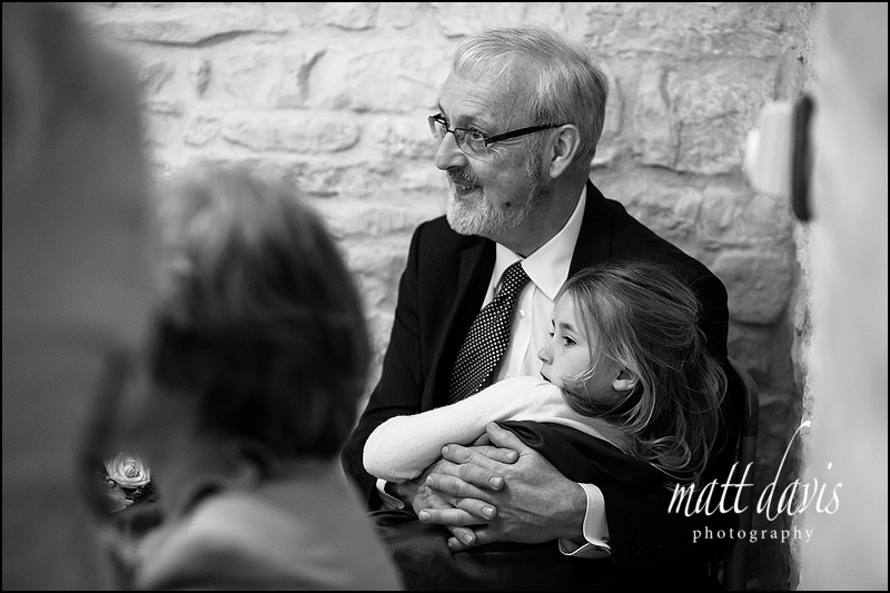 wedding guest at Kingscote Barn with bridesmaid on his lap