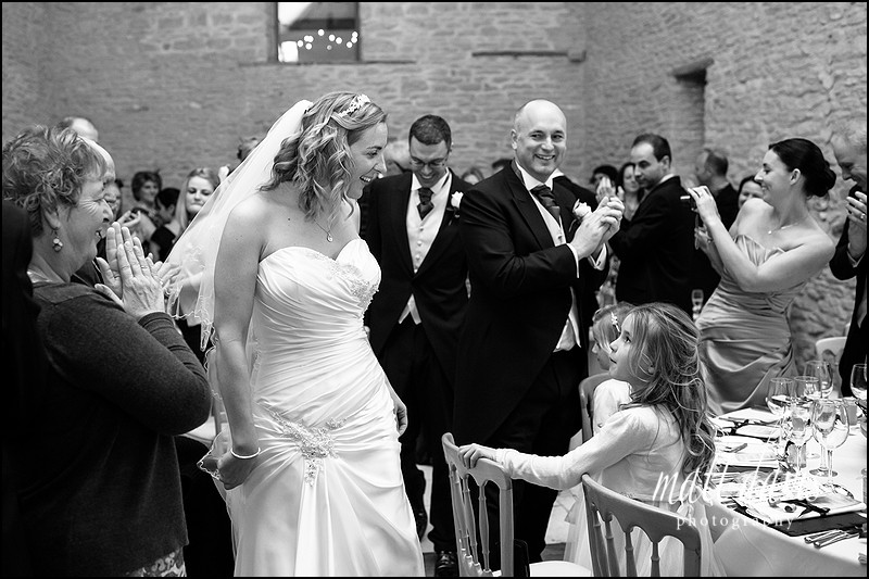 black and white Kingscote Barn wedding photo as bride and groom enter barn