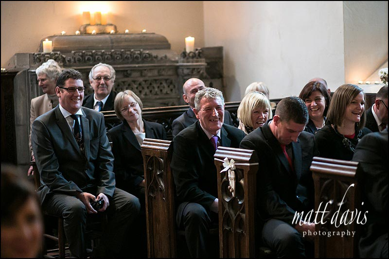 Wedding guests laughing during the vicars service at St. Leonard's Church, Stanton Fitzwarren