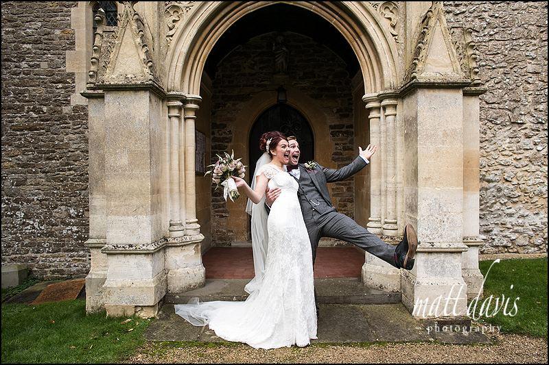 Fun wedding photos of bride and groom outside St. Leonard's Church, Stanton Fitzwarren