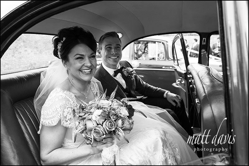 Vintage wedding car with stylish bride and groom