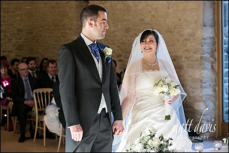 Bride smiling at groom during civil wedding ceremony at Kingscote Barn