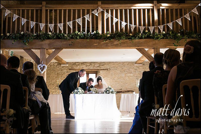 Inside Kingscote Barn signing the register during a winter wedding ceremony