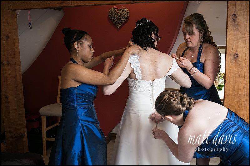 wedding dress being buttoned up by bridesmaids
