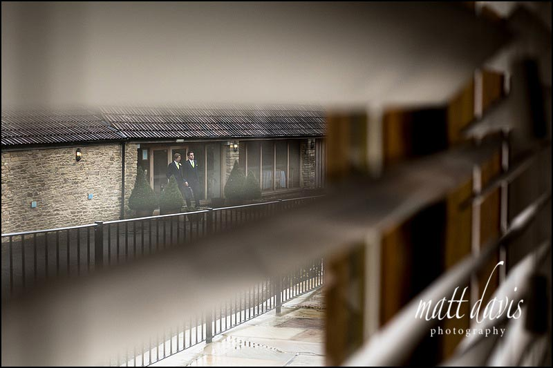 Ushers waiting outside Kingscote Barn for wedding guests