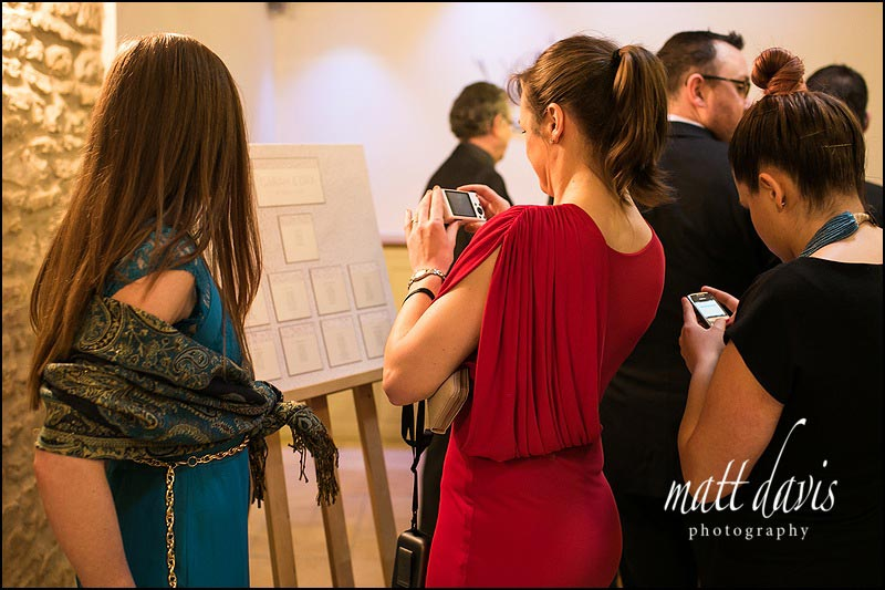 Guests photographing the table plan at Kingscote Barn