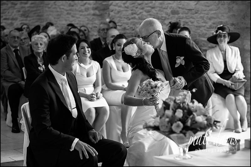 Father of the bride giving her away during a wedding ceremony at Kingscote Barn