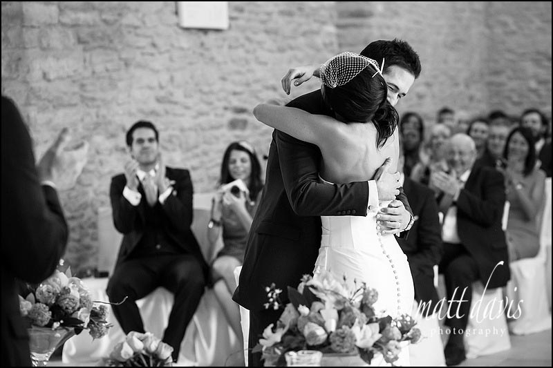 First kiss for bride and groom at Kingcote Barn wedding