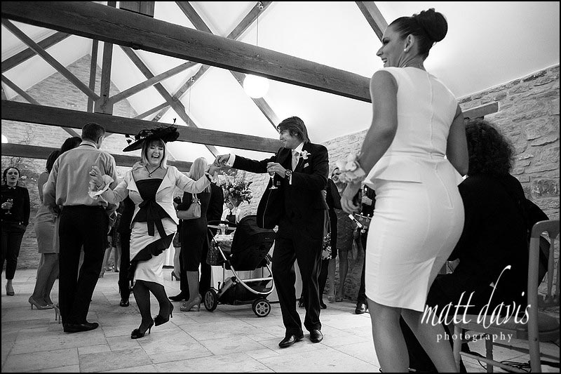 Mother of the bride dancing during a drinks reception at Kingscote Barn
