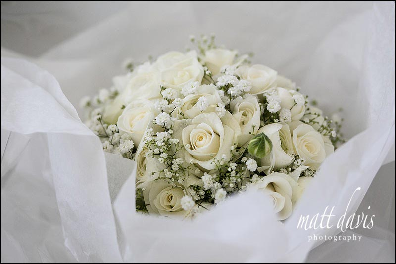 White roses in wedding bouquet with additional flowers