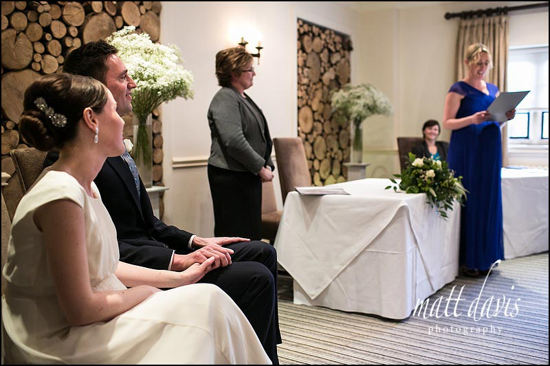 Wedding couple holding hands during wedding ceremony at Manor House Hotel