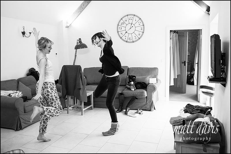 Bridesmaids dancing in the accommodation at Kingscote Barn