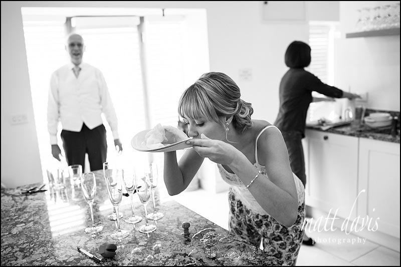 Bridesmaid drinking champagne spillage from plate
