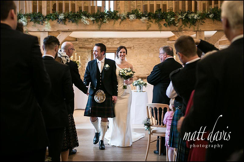 Bride and groom leave a Wedding at Kingscote Barn