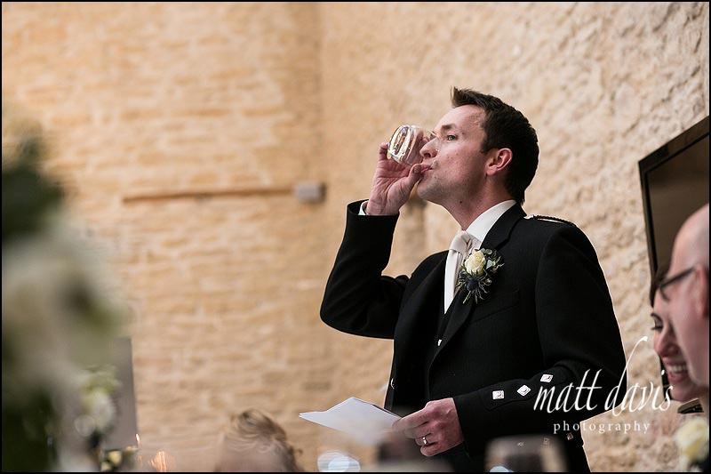 Groom downs his drink during speeches at weddings at Kingscote Barn