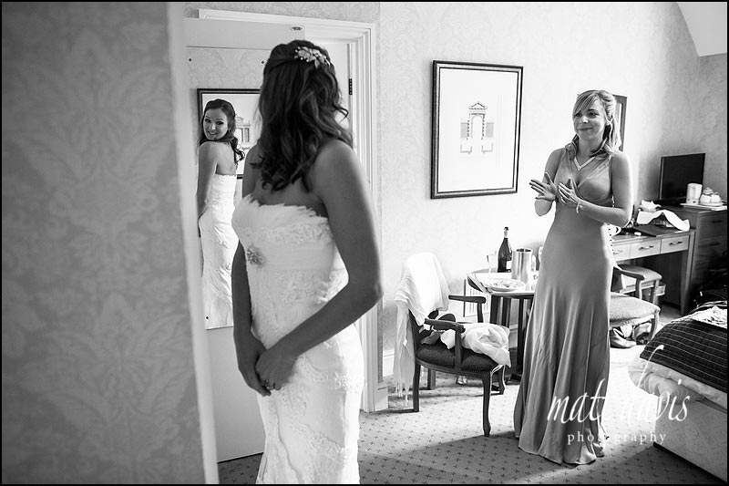 Bride looking at herself in wedding dress at Dumbleton Hall