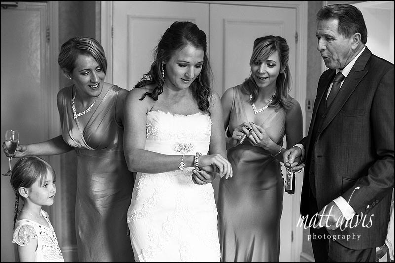 wedding photography at Dumbleton Hall of bride trying on jewellery gift