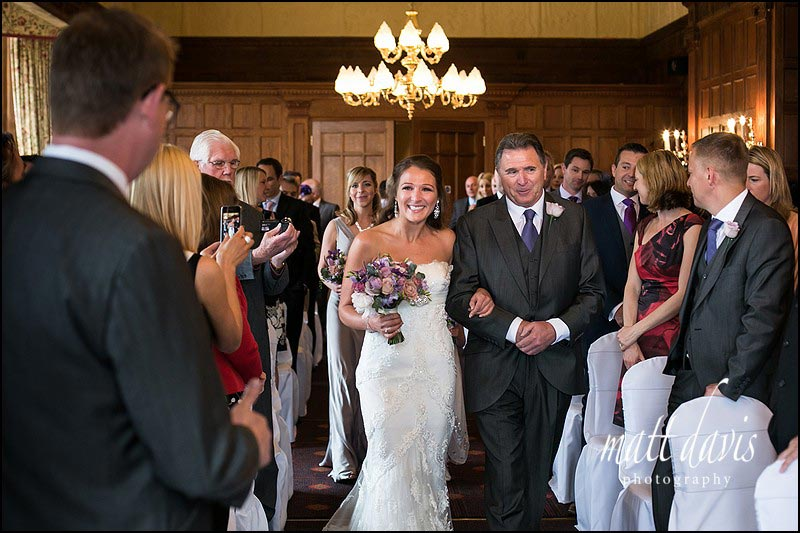 Brides arrival in main wedding ceremony room at Dumbleton Hall