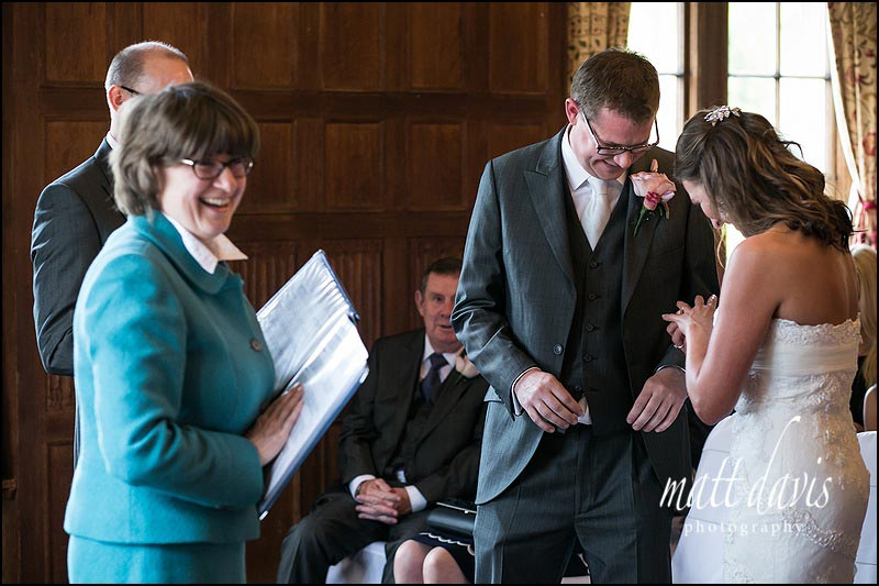 Bride puts on her own ring as groom has hot hands at their wedding at Dumbleton Hall