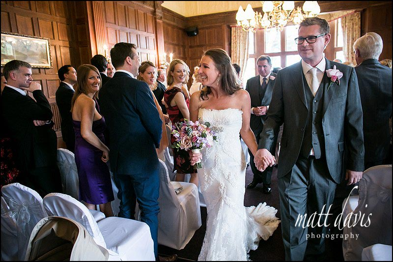 Couple exit wedding ceremony at Dumbleton Hall, Worcestershire