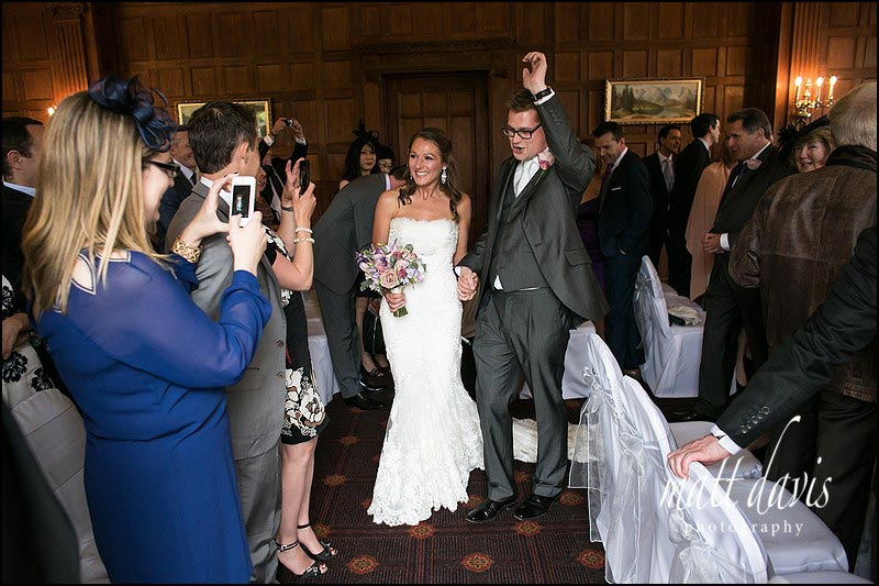 An exuberant groom leaves the wedding ceremony at Dumbleton Hall and punches his arm in the air