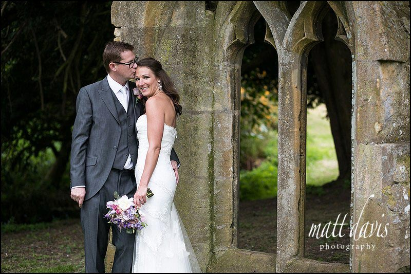 Dumbleton Hall Wedding Photos using the old church window in the gardens