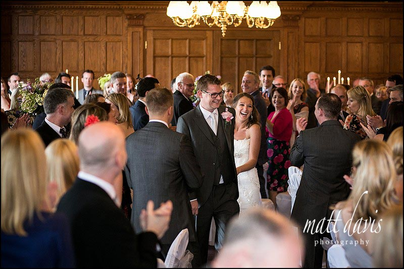 A happy wedding couple entering their wedding breakfast at Dumbleton Hall