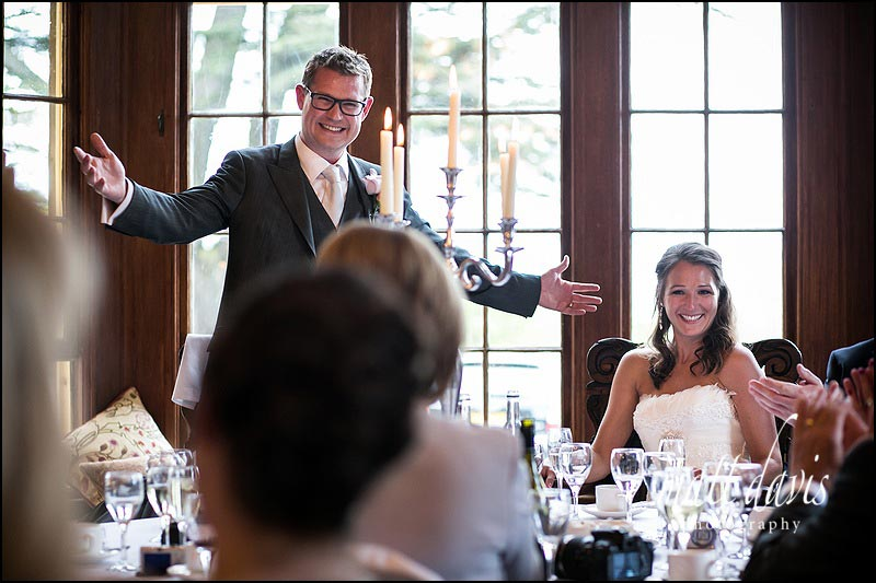 A very animated grooms wedding speech with bride smiling.