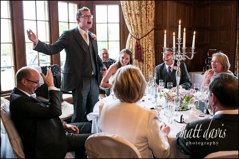 Groom gesticulates during his wedding speech and best man laughs