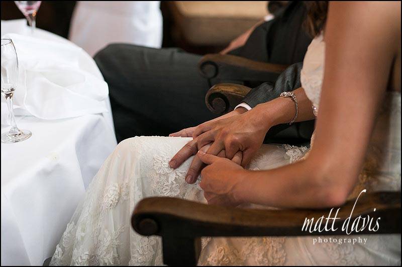 wedding couple holding hands during speeches
