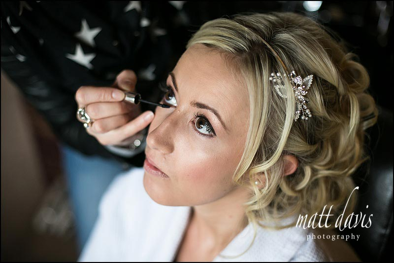Make-up artist applying eye liner to bride who is having her wedding at Friars Court